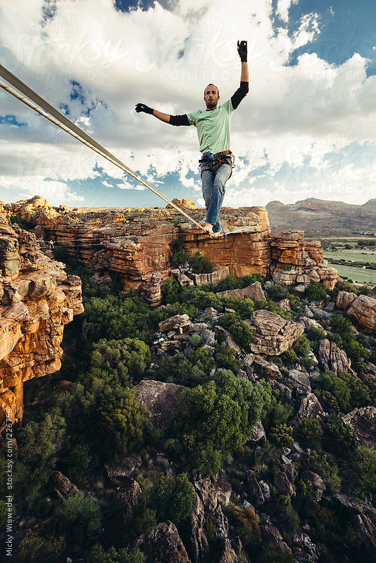 Man balance walking on a highline or tight rope high over a mountain valley at sunset by Mickey Wiswedel