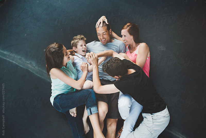 Young family with teenagers having fun wrestling on trampoline by Rob Campbell