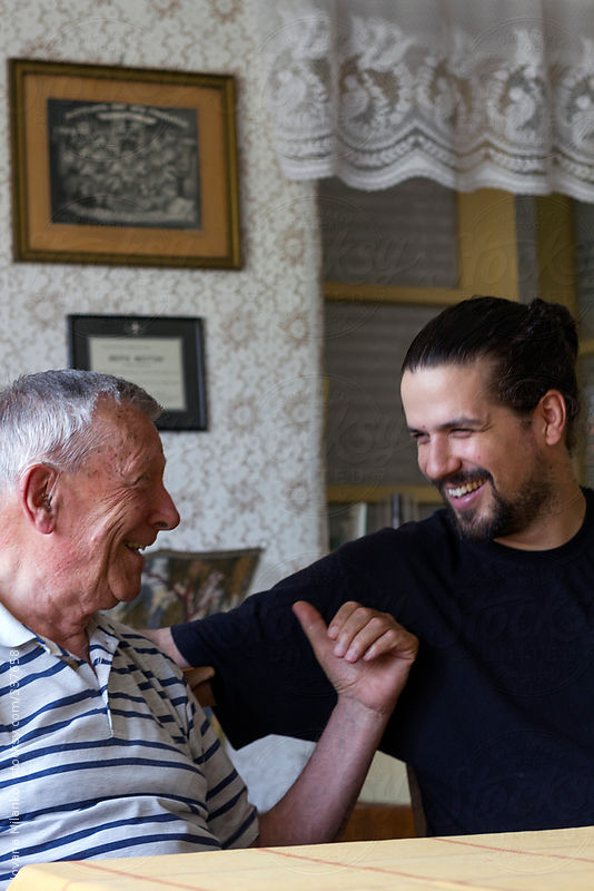 Grandpa and his adult grandson having a laugh by Jovana Milanko