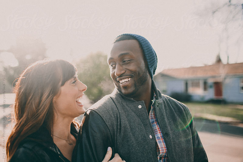 Cute interracial couple walking in neighborhood by Phil Chester Photography