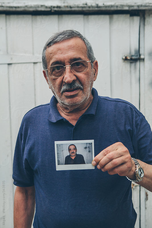 Senior man holding an instant photo of himself. by kkgas