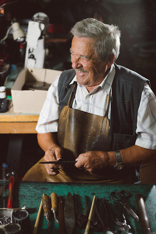 Smiling shoemaker working at his desk by Branislav Jovanović