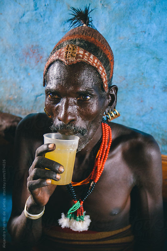 Hamer tribe senior man with traditional clothes having a drink on a local bar. Omo Valley, Ethiopia by Alejandro Moreno de Carlos