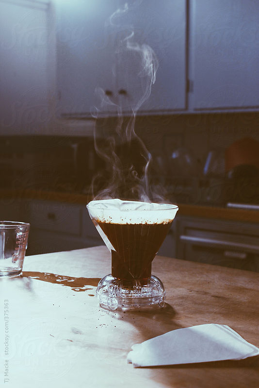 vapor rising from brewing coffee resting on table by TJ Macke