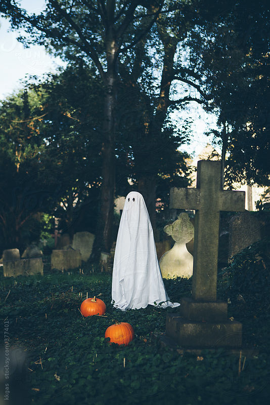 Little boy in halloween ghost costume in a graveyard by kkgas