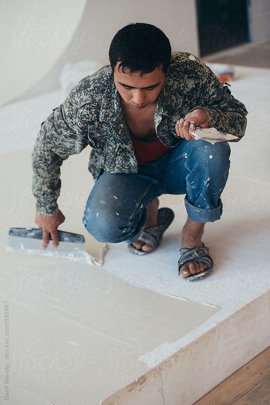 Contractor working with plaster or putty by Danil Nevsky
