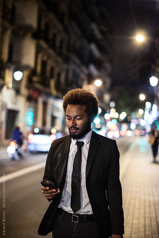 Afro businessman with mobile phone walking on the street at night. by Eduard Bonnin