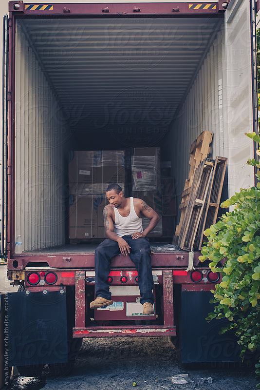 Portrait of a man sitting in an empty container and taking a break by anya brewley schultheiss