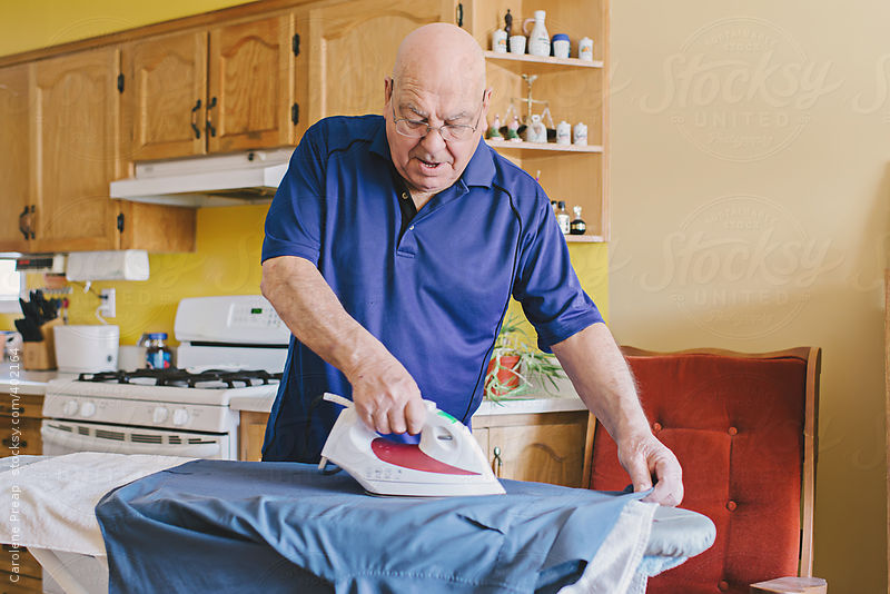 Elderly man ironing clothes by Carolene Preap