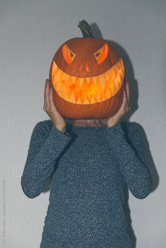 Woman holding glowing carved Halloween pumkin in front of her face by Lior Zilberstein