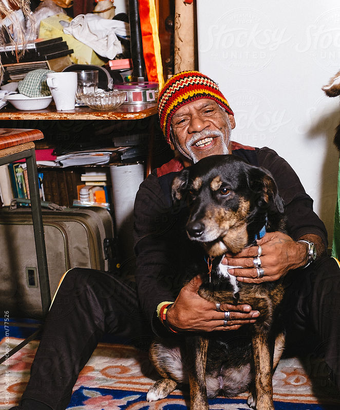 Wurundjeri Elder seated on the floor with his dog by Gary Radler Photography