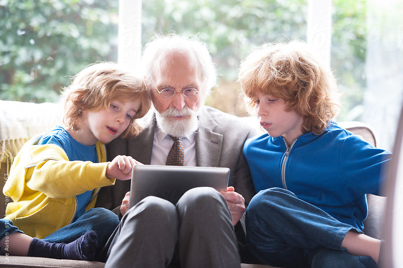grandfather and grandsons using a digital tablet by Lee Avison