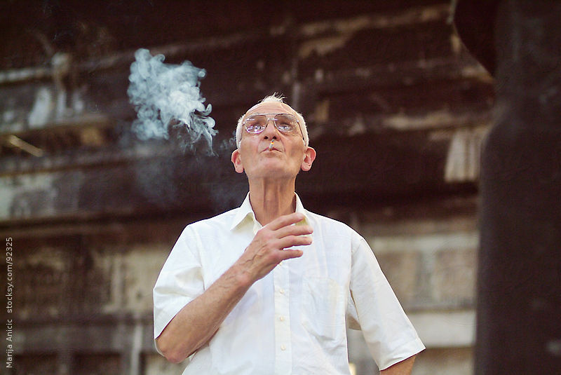 old man smoking in old factory by Marija Anicic