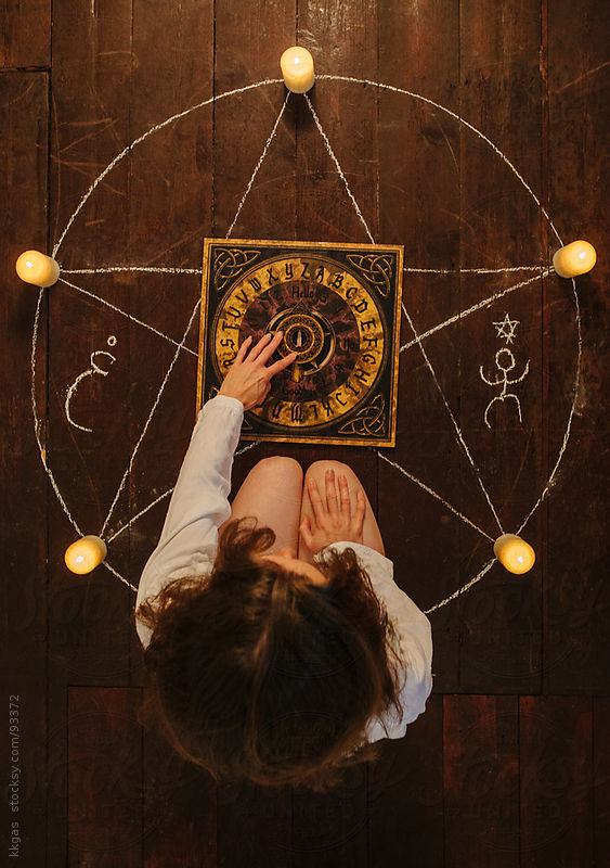 Woman sitting inside a pentagram using a Ouija board by kkgas