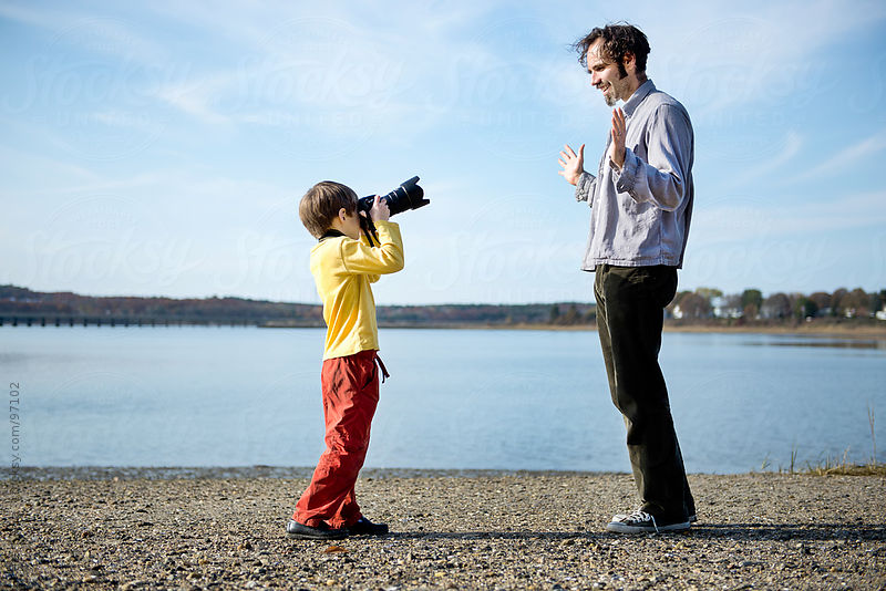 Boy on a beach takes a picture of his father with a digital SLR camera by Cara Slifka
