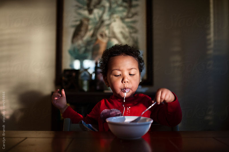 toddler boy eats cereal for breakfast by Carolyn Brandt