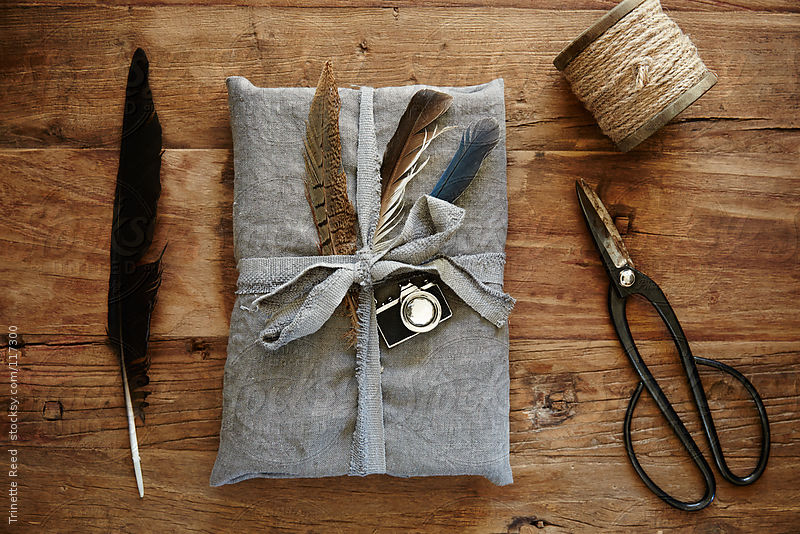 Still life of hipster linen wrapped gift with feathers by Trinette Reed