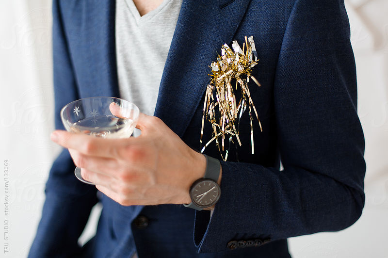Young man in navy suit holding champagne glass at a party with tinsel on white background. by Tru Studio