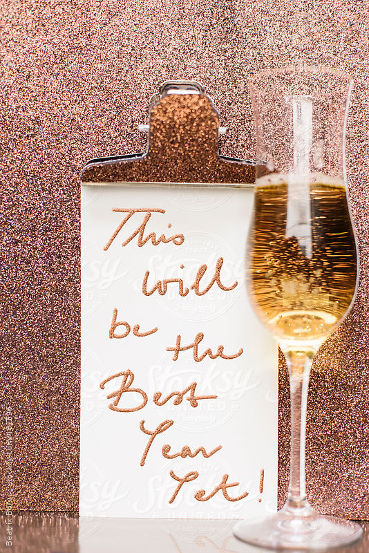 New year message with a glass of champagne in front of a glitter background by Beatrix Boros