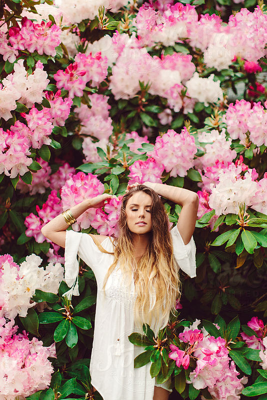 Pretty woman in posing in pink flowers by Kristen Curette