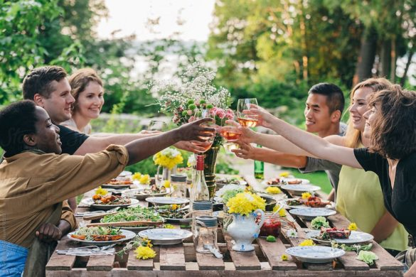 Friends toasting with wine at outdoor summer feast